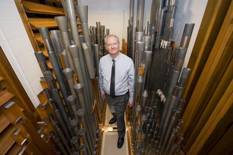 Dean Billmeyer standing among Northrop's organ pipes