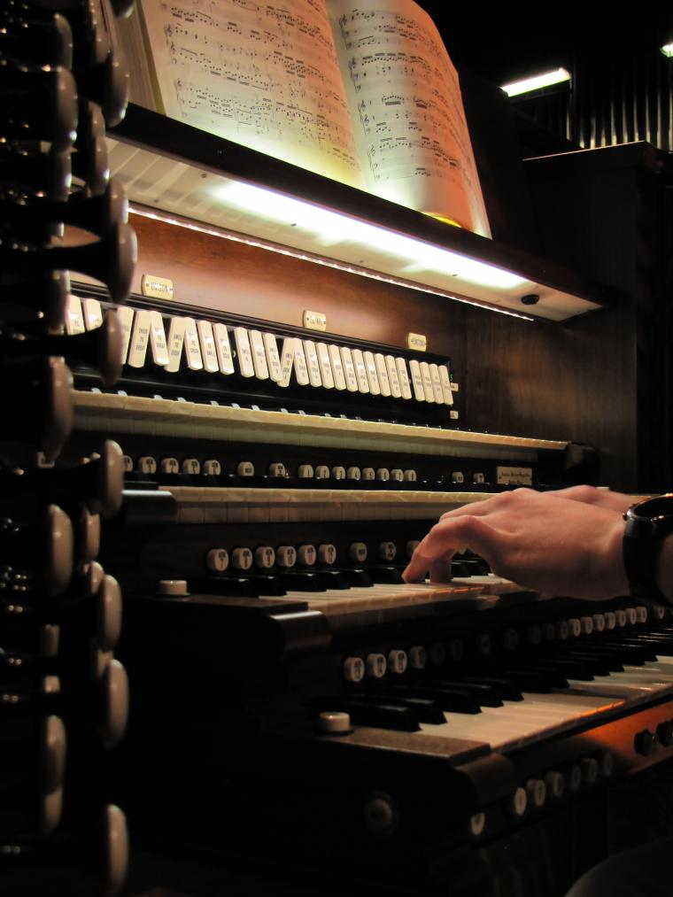 Closeup of hands playing Northrop's organ
