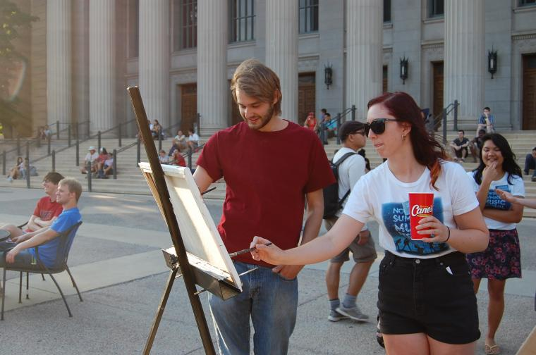 Student group member paints on the plaza