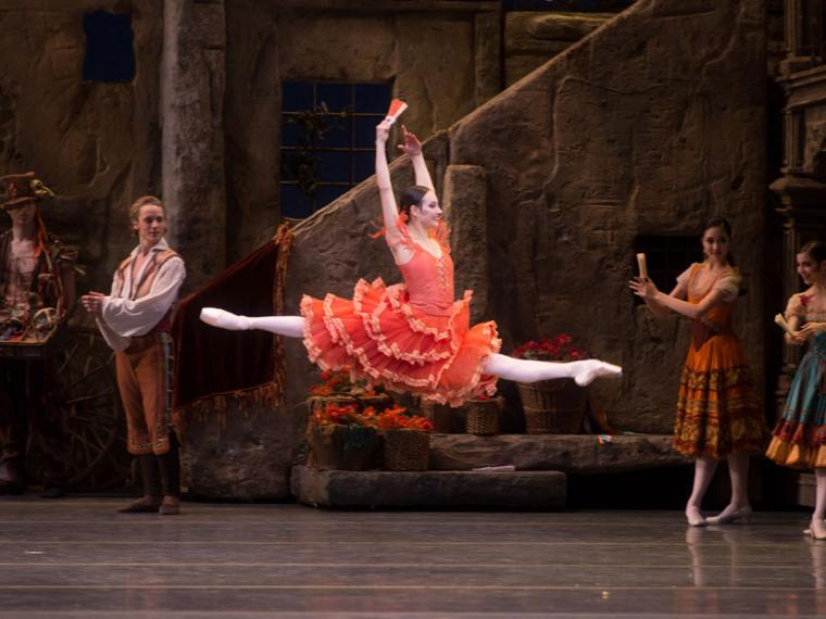 Female performer in a red dress with many ruffles does a split leap across the stage