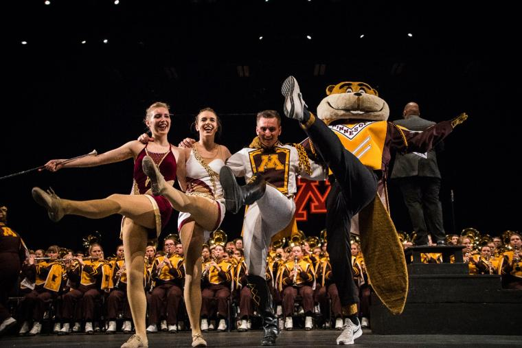 Drum Major team do high-kicks in front of band with Goldy