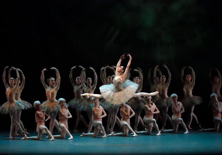 Female dancer in sparkling grayish costume does a split leap high above the stage with a chorus of dancers posing behind her.