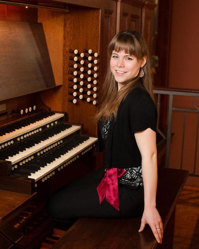 Katelyn Emerson sits at an Organ and smiles towards the camera.