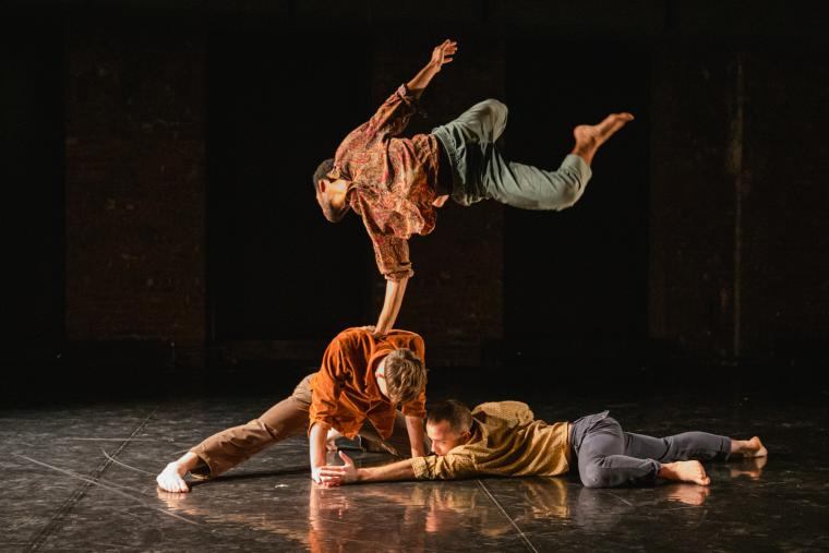 Three male Gallim dancers perform on stage with a black background.