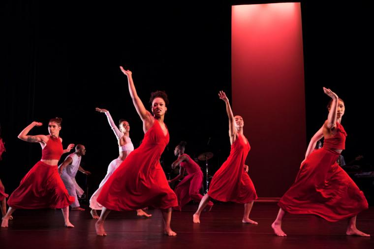 A group of dancers in red dresses perform on stage.