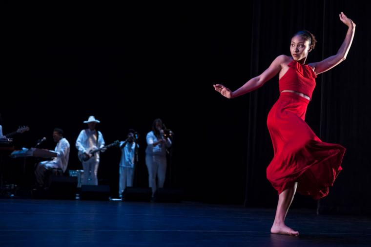 A female dancer performs on stage with as a band plays in the background.