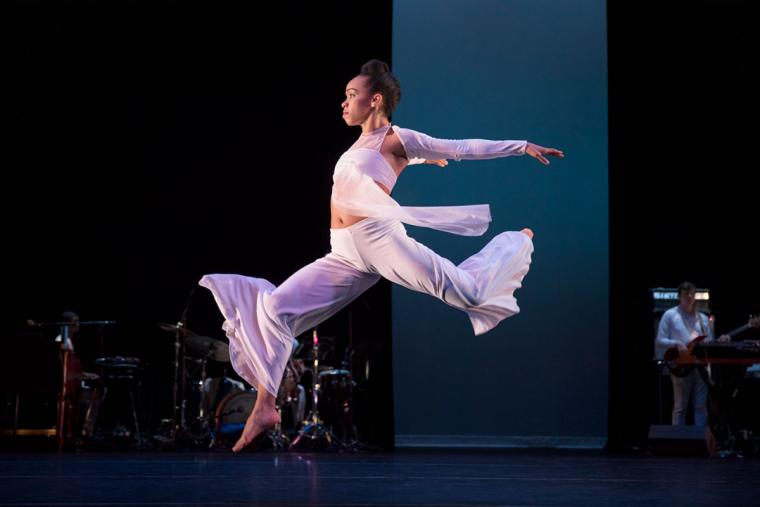 A female dancer wearing white leaps forward on stage.