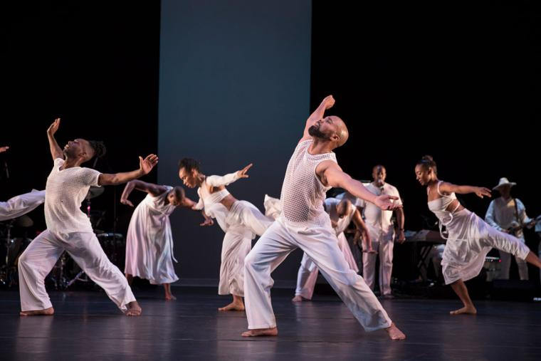 A group of dancers wearing all white perform on stage.