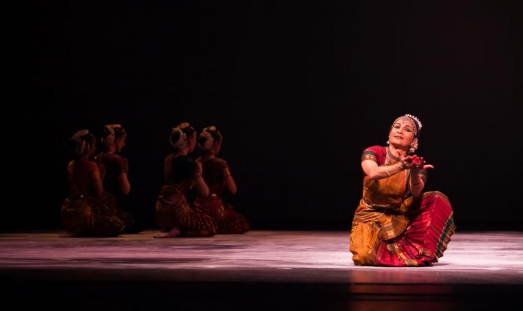 Female dancer in red traditional Indian dress kneels on one knee, hands reaching forward with palms up like a cup