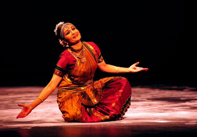 Female dancer in red traditional Indian dress sits cross-legged, smiling and leaning slightly to one side with her elbows in and hands reaching out.