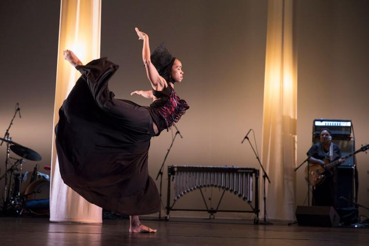 A female dancer poses on stage with lit columns behind her.