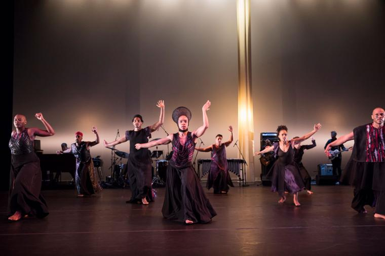 A group of dancers perform together on stage.