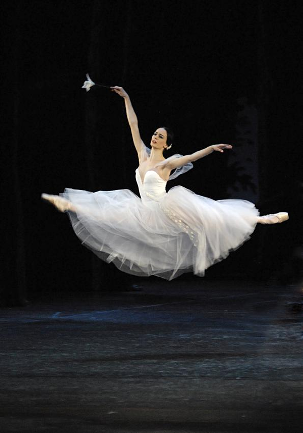 Lead dancer in long white tutu leaps high above the stage