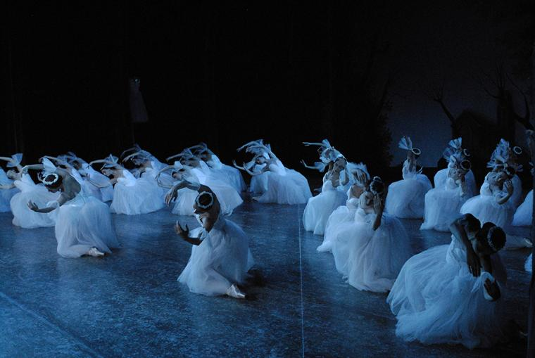 Large group of female dancers in white under a blue light, each on one knee, leaning to the side with rounded arms framing their heads