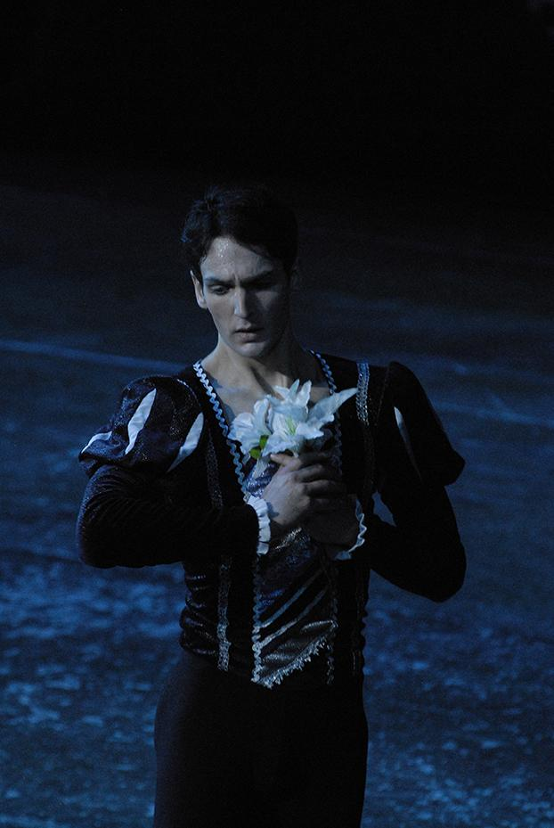 Male dancer holds flower to his chest, eyes cast down to the side