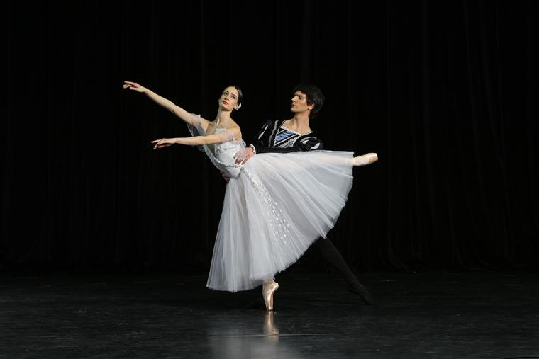 Ballerina on pointe in arabesque, arms out with her partner holding her waist