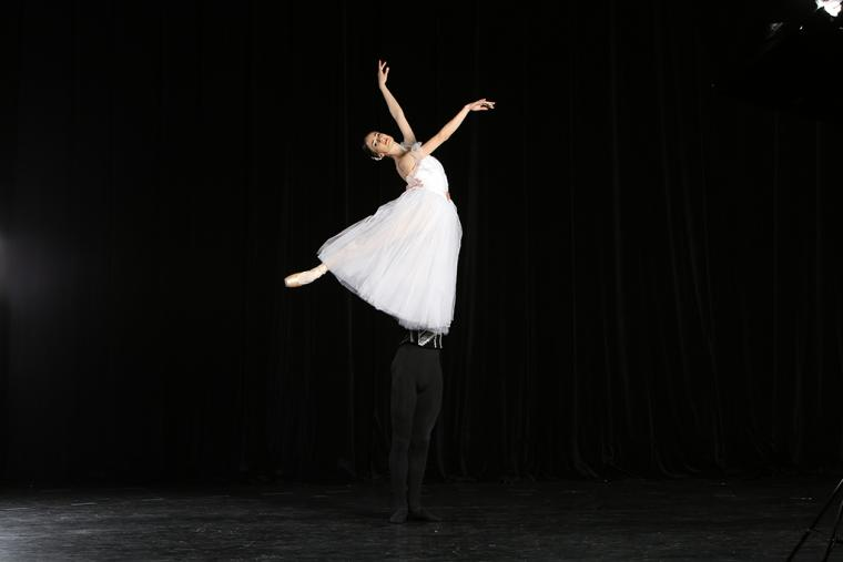Lead dancer poses while lifted high above the stage, her partner is obscured by her gown and it looks as if she's floating above the stage