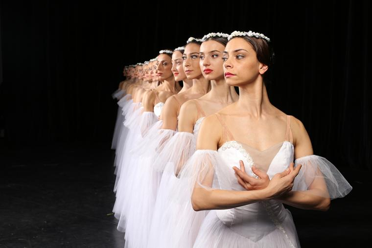 Corps de ballet in a line one behind the other looking to the side, a full view of the front dancer, the others look like a diminishing reflection of her