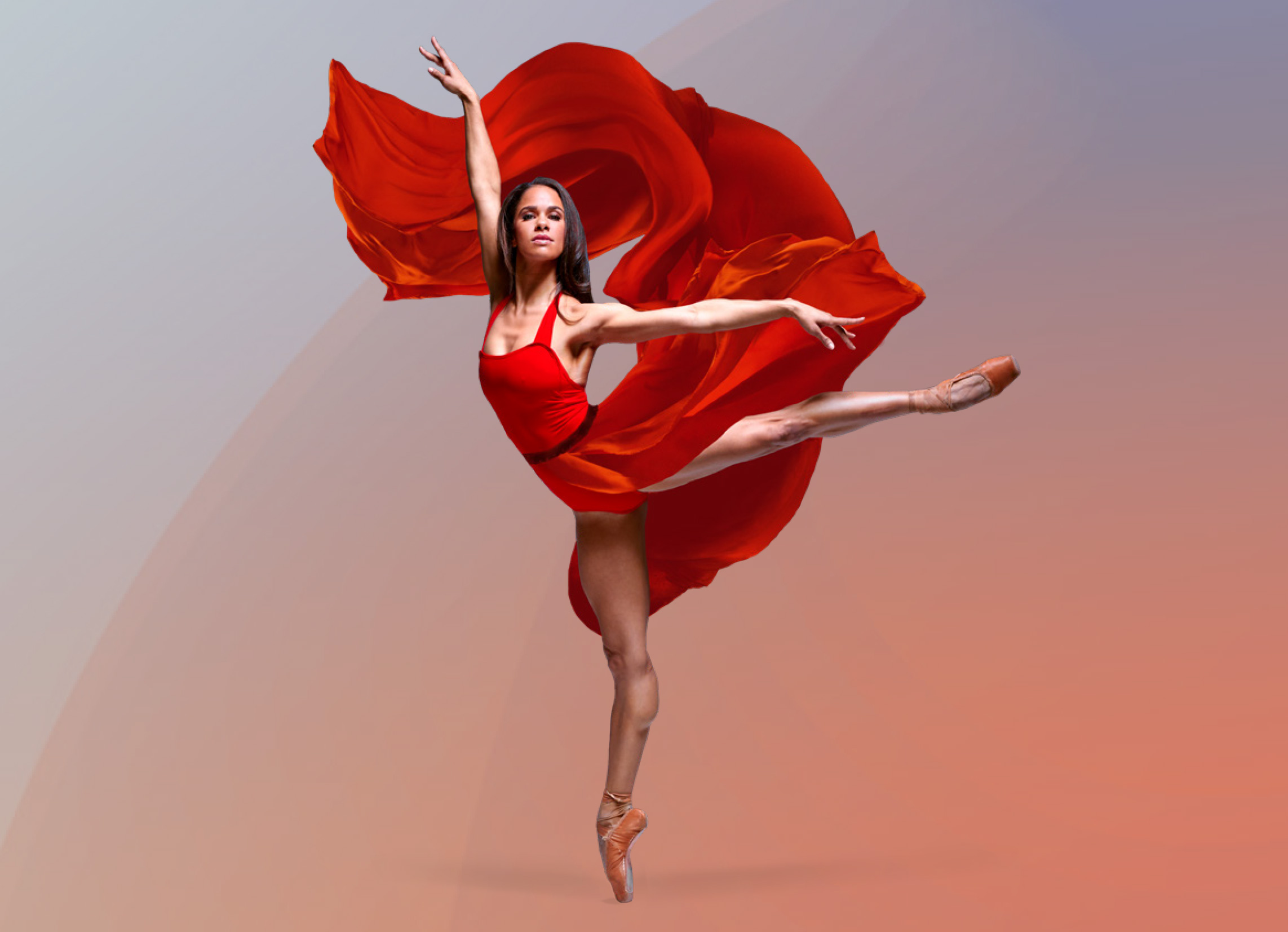Misty Copeland in a red dress standing on pointe