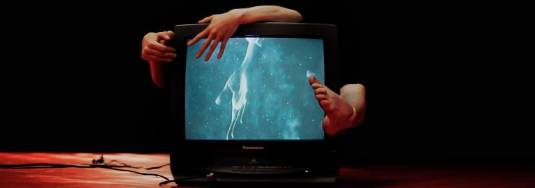 A black & white television is being embraced from behind and has an image of a hand reaching on the screen