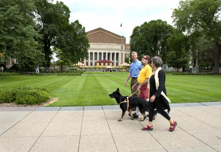 Three people walk with a dog in the University Mall. Northrop is in the background of the image.