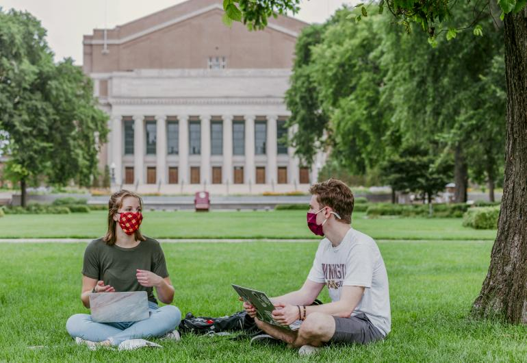 Students sit on lawn with Northrop in the background. Both students are wearing masks and sitting six feet apart.