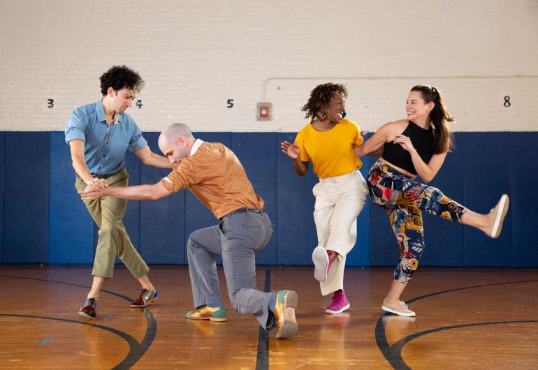Two men and two women in a gymnasium swing dancing.