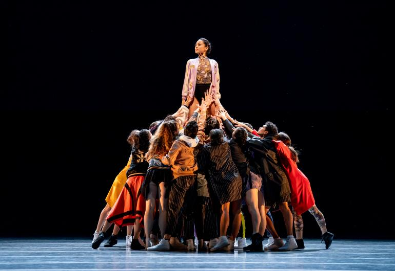 A large group of dancers form a circle and lift up one woman in the middle.