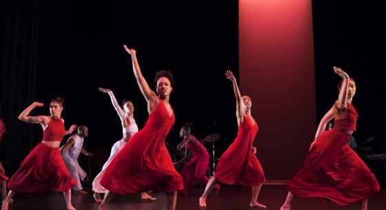 Group of dancers in red one arm raised, legs wide apart