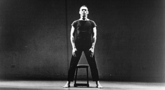 Victor Quijada stands firmly over a stool, legs apart and arms down, in spotlight against black background.