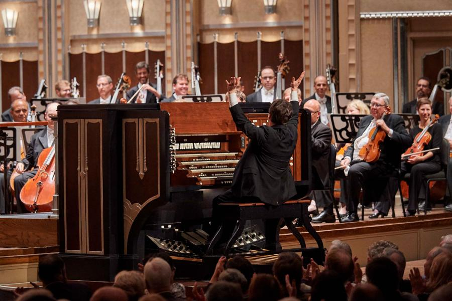 Paul Jacobs plays the organ on stage in front of a full orchestra.