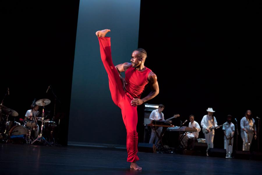 A male dancer wearing all red kicks his leg high on stage as a band plays in the background.