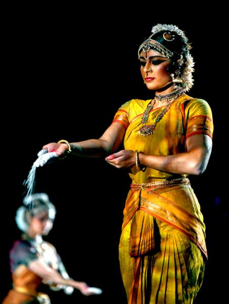Female dancer in gold traditional Indian dress stands focusing as sand falls from her hand to the stage.
