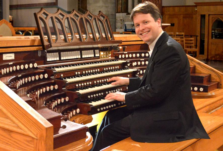 Paul Jacobs sits at the organ looking to side, smiling at the camera