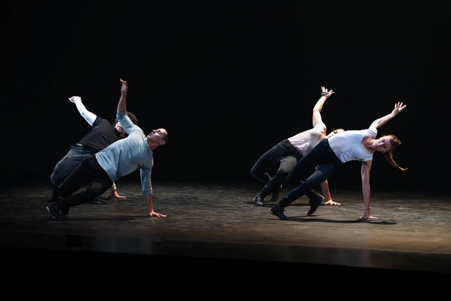 Four dancers in formation arching to the side with one hand on the ground the other reaching up and back