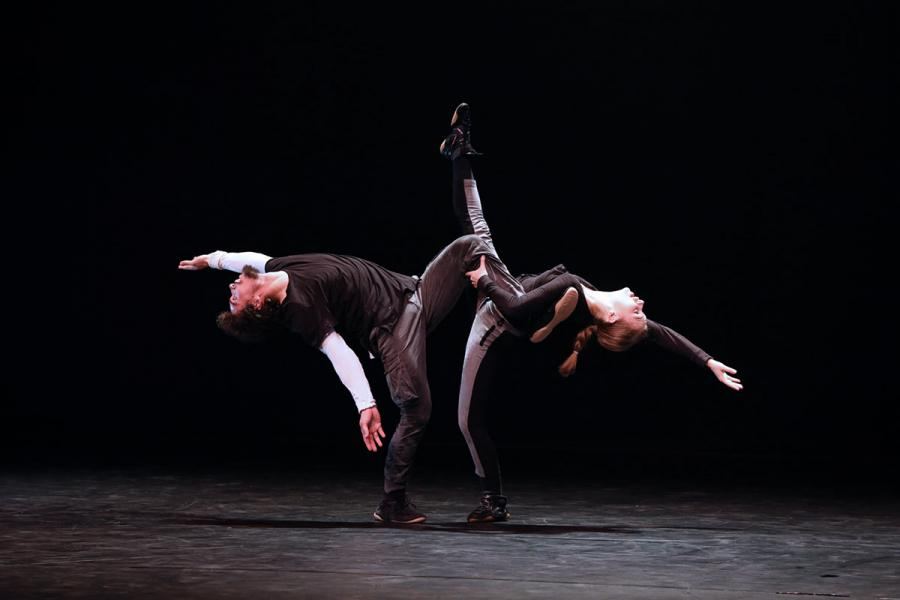Two dancers stand facing eachother on one foot kicking while arching backwards in opposite directions