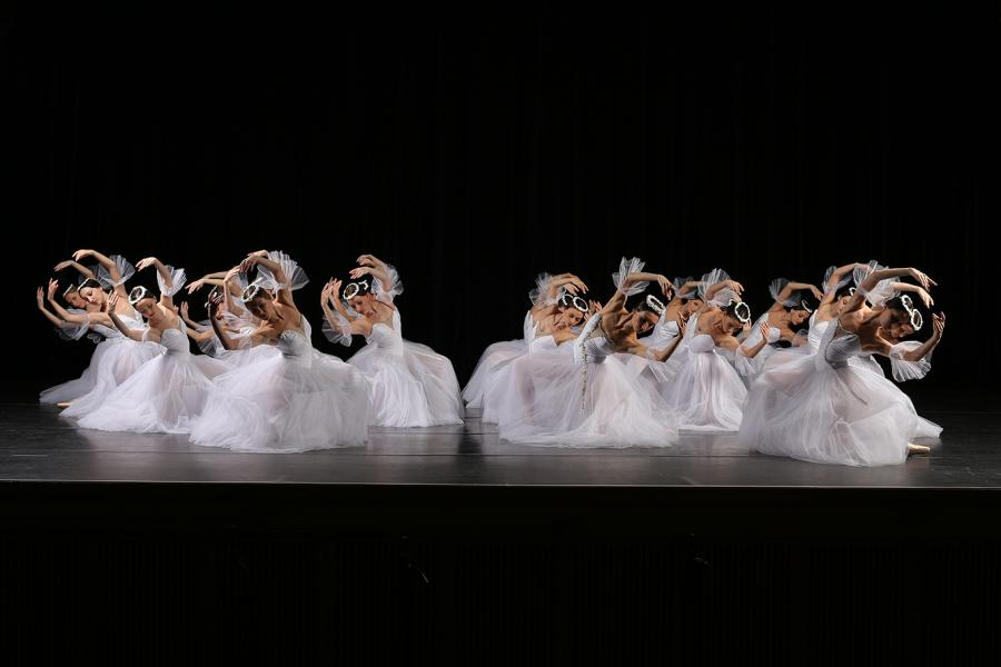 Front view of the corps de ballet in bright white, on one knee leaning to the side with arms circling their heads